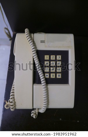 Old white landline phone with cable photo