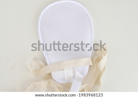 A medical hand restraint mitten showing the net meshing with straps to secure onto wearer's hand to restrict movement and prevent patient from scratching or removing IV and feeding tubes. Royalty-Free Stock Photo #1983968123