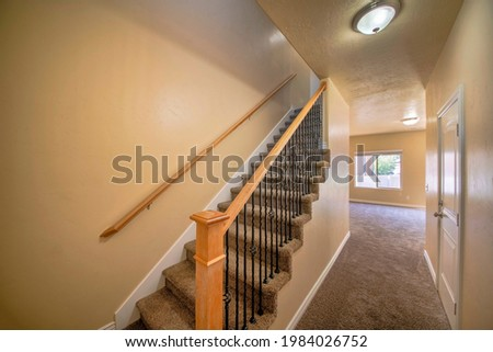 Interior of an empty house with stairs and carpeted flooring. Hallway interior beside the carpeted stairs with wooden handrail and metal baluster, across a closed white door room and windows. Royalty-Free Stock Photo #1984026752