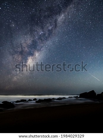 The night sky with Milky Way and meteoroid at Killcare Beach on the Central Coast of NSW, Australia.