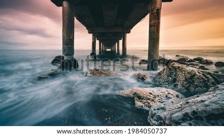 A bottom view of a rocky coast boarding an old wooden pier during a dramatic sunset Royalty-Free Stock Photo #1984050737