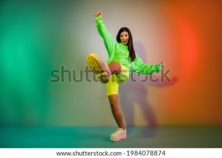 Full length body size view of pretty funky cheerful girl dancing good mood isolated over multicolor vivid neon light background Royalty-Free Stock Photo #1984078874