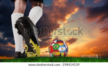 Composite image of football boot kicking flag ball against green grass under dark blue and orange sky #198414539