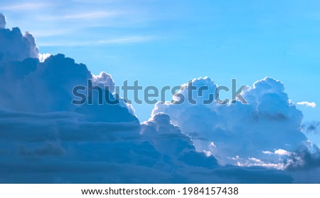 Dramatic light and dark cumulonimbus and cumulus clouds in blue sky background at evening time Royalty-Free Stock Photo #1984157438