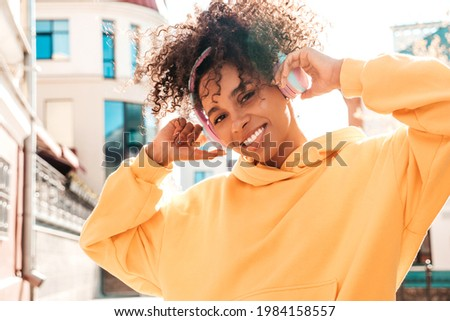 Beautiful black woman with afro curls hairstyle.Smiling model in yellow hoodie.Sexy carefree female enjoying listening music in wireless headphones.Posing on street background at sunset