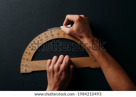closeup of a young caucasian man using a wooden protractor on a dark gray chalkboard