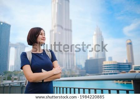 Young beautiful woman enjoying the view of Dubai downtown. Enjoying travel in United Arabian Emirates. Royalty-Free Stock Photo #1984220885