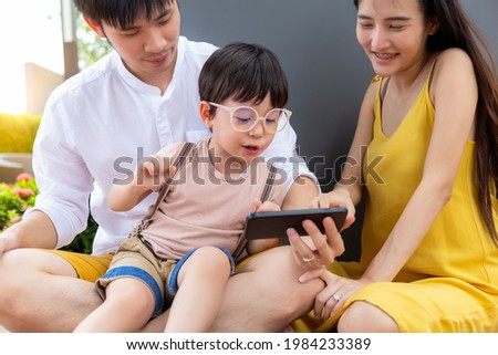 Happy Little young child using smart phone for playing and watching game or cartoon on internet online with family Lovely children stay with parent on weekend holiday Father mother and son enjoy life
