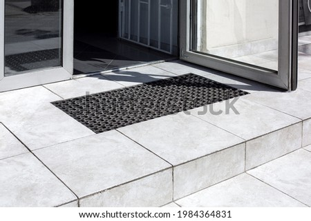 threshold made of light gray ceramic tiles with steps at the entrance to the store with a foot mat and an open glass door at the facade of an office building close-up, nobody. Royalty-Free Stock Photo #1984364831