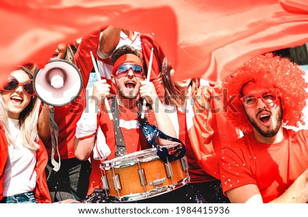 Football supporter fans cheering with flag watching soccer cup match at stadium tribune - Young people group with red t-shirt having excited fun on sport championship - Bright vivid filter Royalty-Free Stock Photo #1984415936