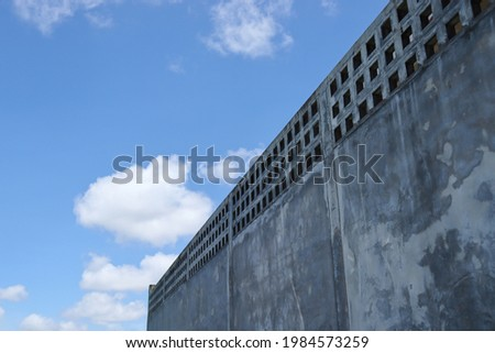 The high wall fence line is made of cement. with a background of sky and clouds during daytime. Construction of walls to create boundaries. Royalty-Free Stock Photo #1984573259