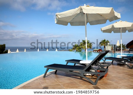 Chaise longues and beach parasols near infinity pool at resort Royalty-Free Stock Photo #1984859756