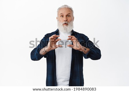 Amazed old man shows credit card, say wow and gasp surprised, recommend bank company, standing against white background