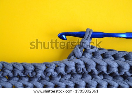 Grey textured knitwear, blue hook lying on a yellow background.Handmade concept, crocheting process, hobby, online course on knitting fashion items, knitted interior items, bags.Copyspace