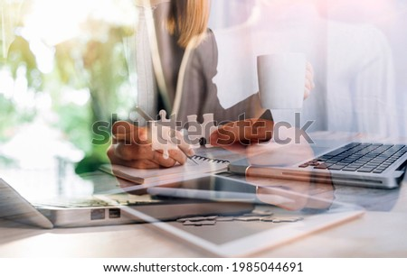Cropped shot group of businesspeople using graph chart and computer laptop, tablet discussing about business plan together in modern office. Royalty-Free Stock Photo #1985044691