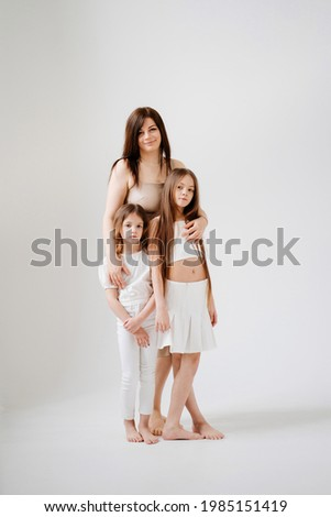 Mom and daughters pose in a white photo studio. Happy family. single mother with children. center for psychological assistance to families. clothing store.