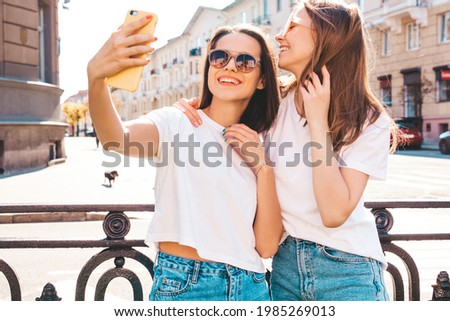 Two young beautiful smiling hipster female in trendy summer white t-shirt clothes and jeans.Sexy carefree women posing on the street background.Positive models having fun, hugging.Taking photo selfie
