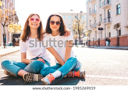 Two young beautiful smiling hipster female in trendy summer white t-shirt clothes and jeans.Sexy carefree women posing on the street background. Positive models having fun, hugging and going crazy Royalty-Free Stock Photo #1985269019
