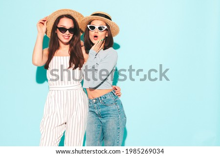 Two young beautiful smiling hipster female in trendy summer  clothes.Sexy carefree women posing near light blue wall in studio.Positive and cheerful models in hats Royalty-Free Stock Photo #1985269034