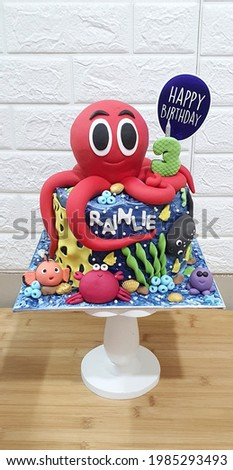 """under the sea and fish theme for kids birthday cake written """" RAINLIE """" and happy birthday paper topper"""