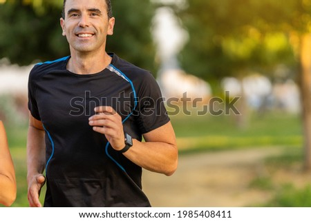 Joyful adult man working out in the park and jogging. He is smiling and looking at front. Royalty-Free Stock Photo #1985408411