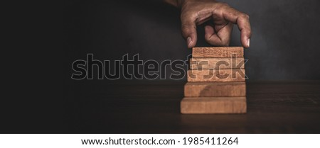 Close-up hand is placing wood block tower stacked in stair step with caution to prevent collapse or crash concepts of financial risk management and strategic planning. Royalty-Free Stock Photo #1985411264