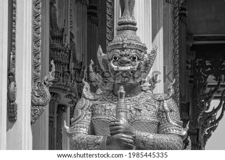 Black and white picture of giant temple guardian Yaksha at Wat Don Mueang Phra Arramluang buddhist temple in Bangkok Thailand.