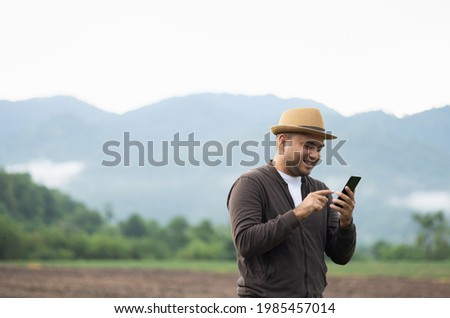 Young Asian men travel to beautiful nature. He stood by the roadside He uses the telephone to communicate. With good phone signal Royalty-Free Stock Photo #1985457014