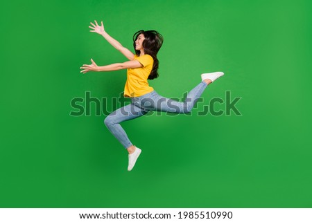 Full length body size side profile photo dreamy girl brunette jumping running catching isolated vibrant green color background