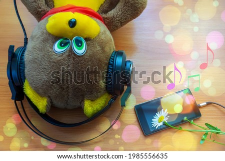 concept of music for young children. a toy bear listens to music from a smartphone with headphones