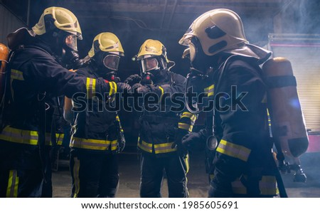 Group of firemen in the fire department organizing action plan for safe execution with gas masks Royalty-Free Stock Photo #1985605691