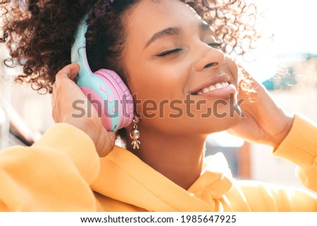 Beautiful black woman with afro curls hairstyle.Smiling model in yellow hoodie.Sexy carefree female enjoying listening music in wireless headphones.Posing on street background at sunset.Closed eyes