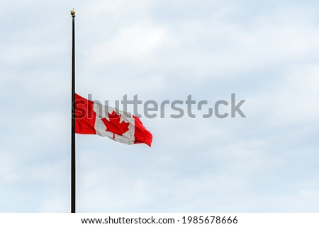 A Canadian flag at half mast, lowered in remembrance of the indigenous children who were abused and died in residential schools. Overcast, wide view. Royalty-Free Stock Photo #1985678666