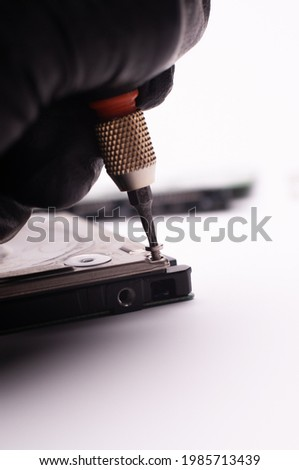 detail of the hard disassembled hard disks with a screwdriver on the hard disk, hard disk maintenance concept