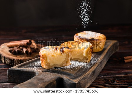 Delicious homemade Belem cakes that are sprinkled with icing sugar on a rustic dark wood table. Cream cakes.