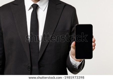 Close up cropped photo portrait shot young employee business corporate man in classic formal black suit shirt work in office hold mobile phone blank screen workspace area isolated on white background