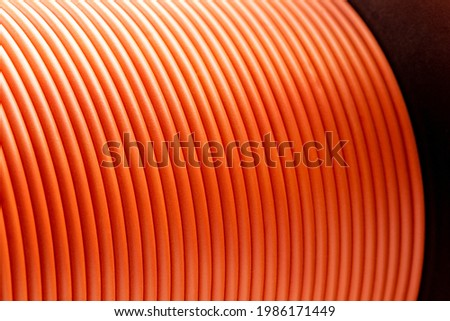 Orange copper wire cable in reels at factory, close up Royalty-Free Stock Photo #1986171449