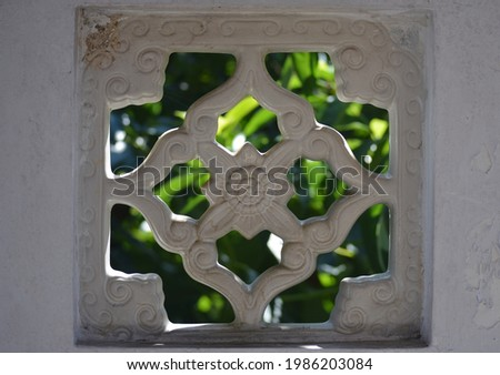 BALI, INDONESIA - MAY 23th, 2021. Unique wall architecture with leaves background and backlight object