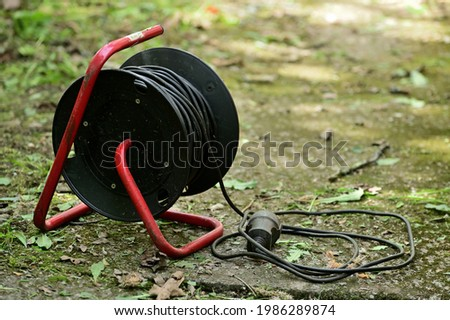 Extension cord on reel with bracket. Part of the wire is wound and lies nearby. The bracket rests on concrete slabs. Royalty-Free Stock Photo #1986289874