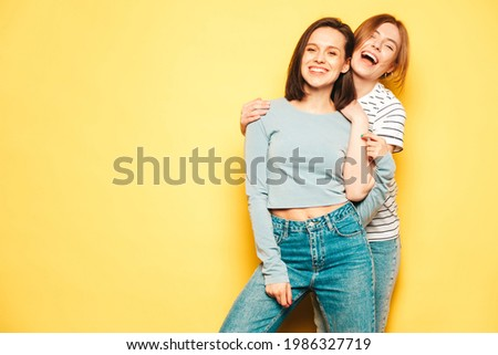 Two young beautiful smiling hipster female in trendy summer white t-shirt and jeans clothes.Sexy carefree women posing near yellow wall in studio.Positive and cheerful models