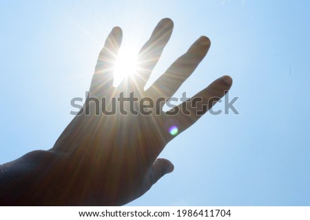 Hot summer sunlight rays pouring through human hand. Hand covering sun light heat temperature.