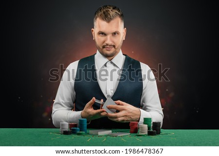 Male dealer at the casino at the table. Casino concept, gambling, poker, chips on the green casino table Royalty-Free Stock Photo #1986478367