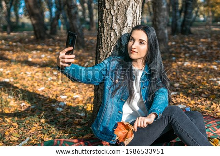 A young woman takes a selfie on her smartphone while sitting by a tree in an autumn park. a woman holds a bouquet of autumn leaves and takes pictures of herself on her phone