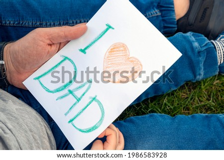 I love dad gift card in father`s hands as present from son in his birthday. Child`s handmade postcard crafts. Family, parenthood, family relationships. Happy Father`s Day.