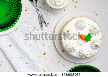 Carrot cake with icing and sprinkles at an Easter party from above with a white background
