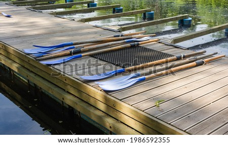Classic wooden boat oars. Plastic boat paddles lie on a wooden pier, boat rental in the park Royalty-Free Stock Photo #1986592355