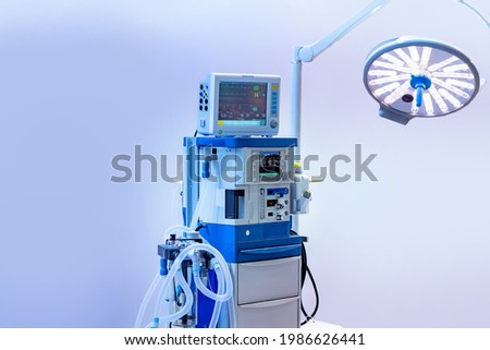 Anesthesia and respiratory apparatus against light background. Anesthesia and respiratory apparatus with lamp to illuminate operation. Equipment for administration human in anesthetized. Royalty-Free Stock Photo #1986626441