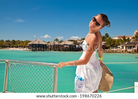 Elegant sexy woman in white summer dress standing near railings on deck. Woman resting on the water. Summer Caribbean vacation. #198670226
