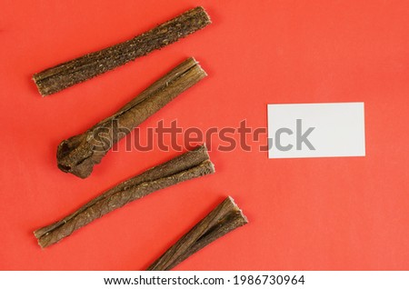 Marketing and advertising of animal products concept. Dog treats and a white blank business card on a red background. Dried beef stomach sticks. Natural dried goodies for dogs. Pet.