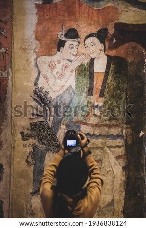 A tourist girl taking pictures of an ancient mural painting of man whispering to woman by digital camera. Wat Phumin, Buddhist temple in Nan, Thailand. The temple is open to the Public. Focus on mural